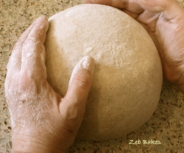 Zeb Bakes shapes a boule