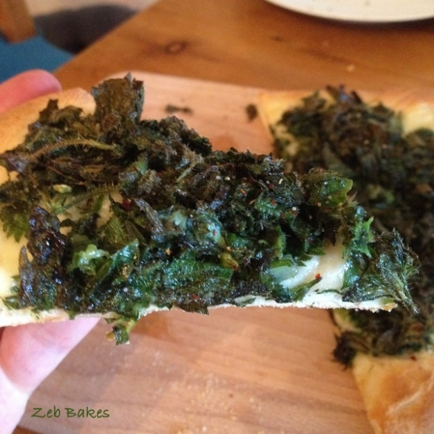 A slice of pizza topped with tender and subdued nettles